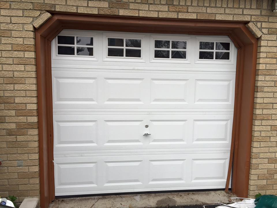 After - New white, insulated garage door with windows after being replaced by Aviya's Garage Door
