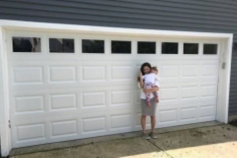 A mother and young child stand in front of their recently repaired double garage door by Aviya's Garage Door.