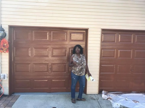 A happy woman stands in front of her newly installed and painted garage doors from Aviya's Garage Door.