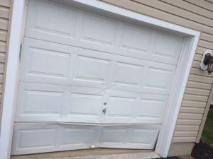 Damaged garage door before being repaired by Aviya's Garage Door company.